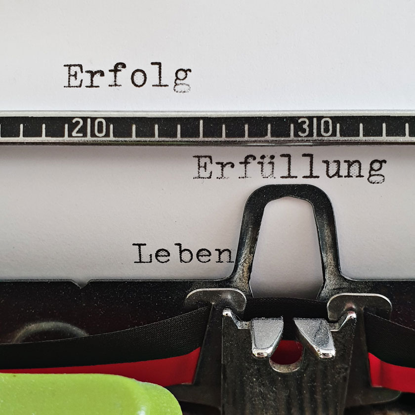 Schreibmaschine mit den Wörtern Erfolg, Erfüllung und Leben